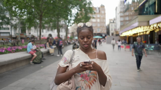 a young woman walking in the busy city streets in the late afternoon - feature phone stock videos and b-roll footage