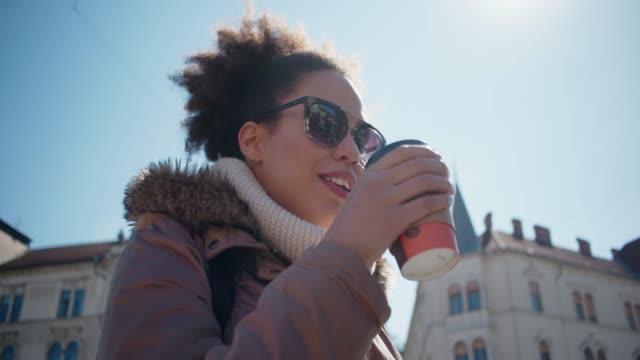 Junge Frau zu Fuß in die Innenstadt und Take away Kaffee trinken