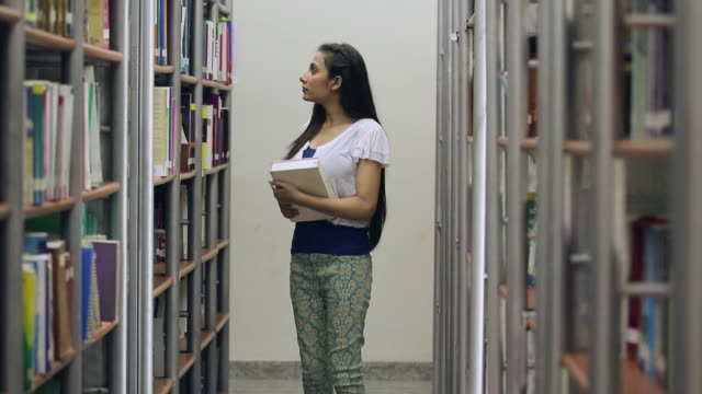 young woman walking in the library, uttar pradesh, india - choosing stock videos and b-roll footage
