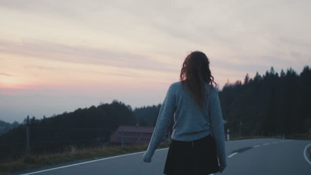 young woman walking in the middle of the road in evening - middle of the road stock videos & royalty-free footage