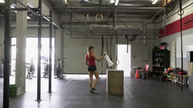 WS Young woman walking into a gym getting ready to work out.