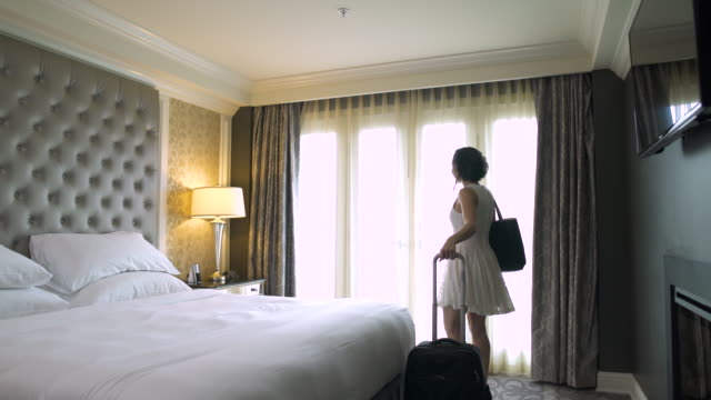 young woman walking into a hotel room and pulling curtains open - wheeled luggage stock videos and b-roll footage