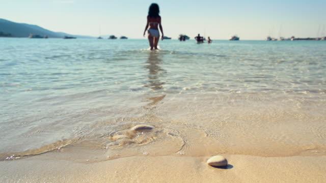 Young woman walking into calm sea