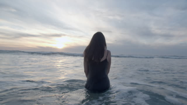 rv young woman walking into the water - kälte stock-videos und b-roll-filmmaterial