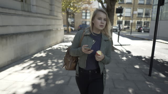A young woman walking looking around and starring at her phone.