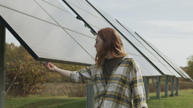 young woman walking next to solar panels in a field - sustainable energy stock videos & royalty-free footage