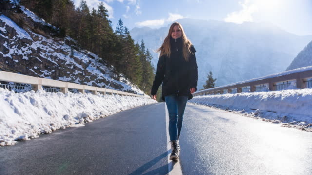 Young woman walking on a bridge in mountainside in winter