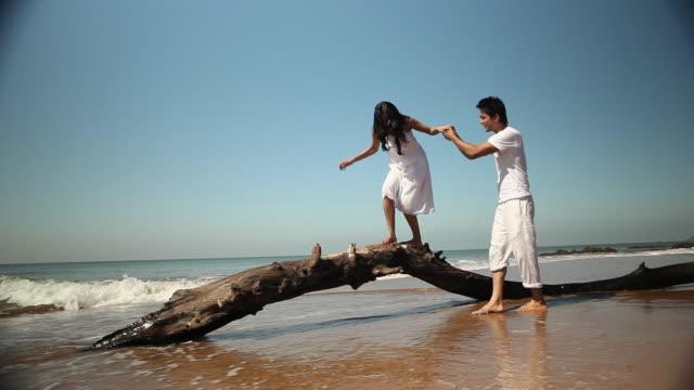 vidéos et rushes de young woman walking on a fallen tree with the help of his boyfriend - se tenir par la main
