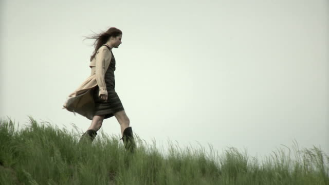 stockvideo's en b-roll-footage met young woman walking on a hill - werkneemster