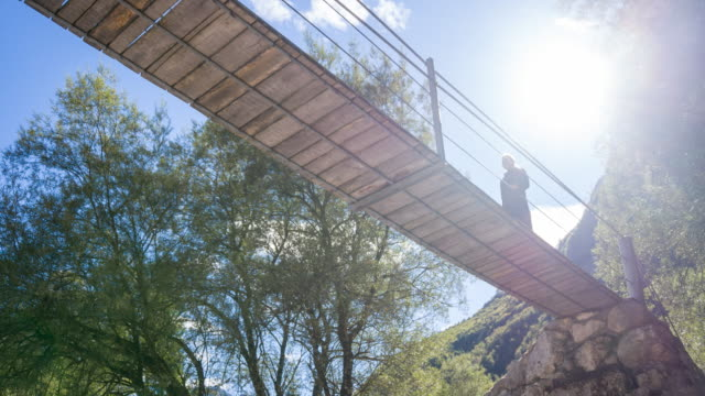 Young woman walking on a wooden suspension bridge above camera