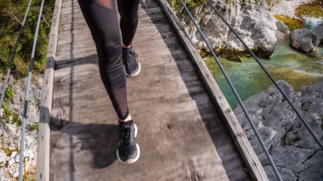 junge frau zu fuß auf eine hölzerne hängebrücke über einen bach - hängebrücke stock-videos und b-roll-filmmaterial