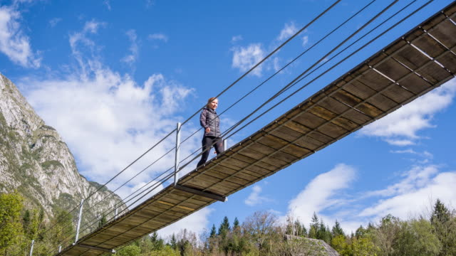 young woman walking on a wooden suspension bridge - high up stock videos & royalty-free footage