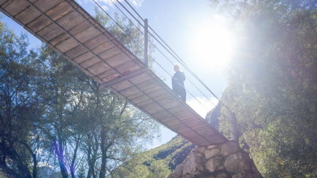 Young woman walking on a wooden suspension bridge