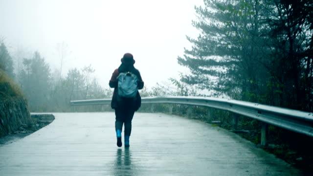 vidéos et rushes de jeune femme marchant sur route brumeuse solitaire - transylvanie