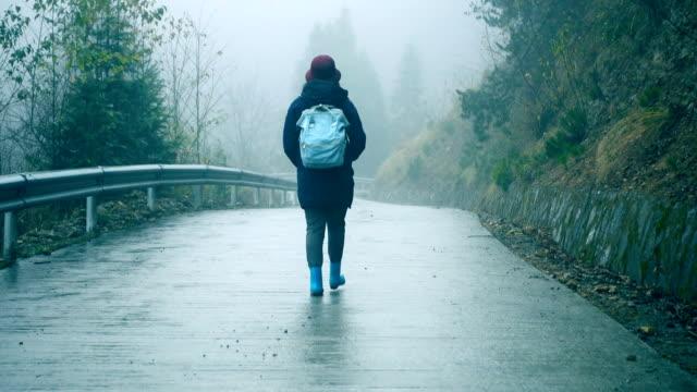 孤独な霧の道の上を歩く若い女性 - バッグ点の映像素材/bロール
