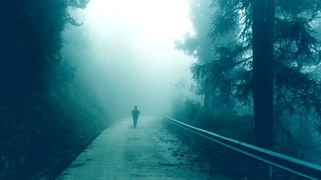 young woman walking on foggy road lonely - loneliness stock videos & royalty-free footage