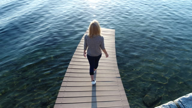 Young woman walking on lake pier, arms outstretched