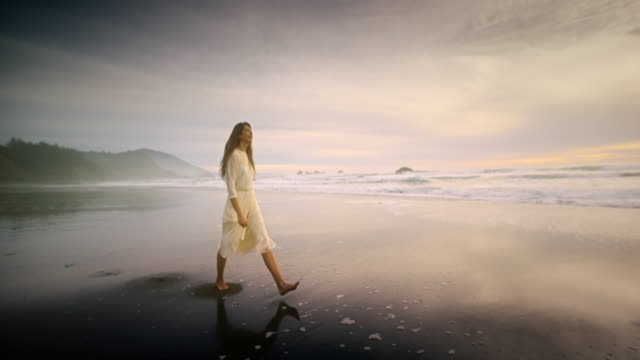 Young woman walking on Ocean Beach at Sunset