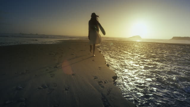 young woman walking on ocean beach at sunset - cliff点の映像素材/bロール