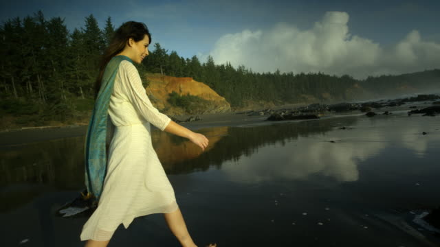 young woman walking on ocean beach at sunset - tide pool stock videos and b-roll footage
