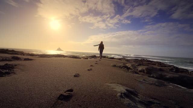 vidéos et rushes de young woman walking on pacific beach at sunset, oregon - empreinte de pas
