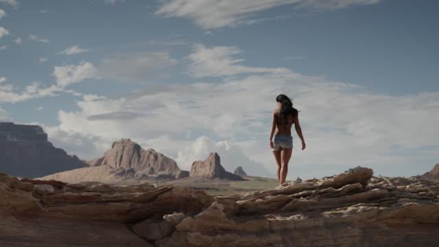 vídeos de stock, filmes e b-roll de ws ds young woman walking on rocks near lake powell / utah, usa - lake powell