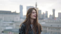 Young woman walking on roof and smilling