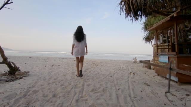 vídeos de stock e filmes b-roll de young woman walking on sandy beach on summer vacations in indonesia - vista traseira