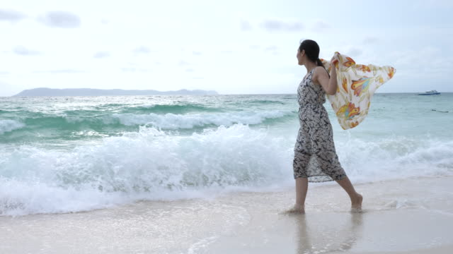 Young woman walking on sea with Scarf