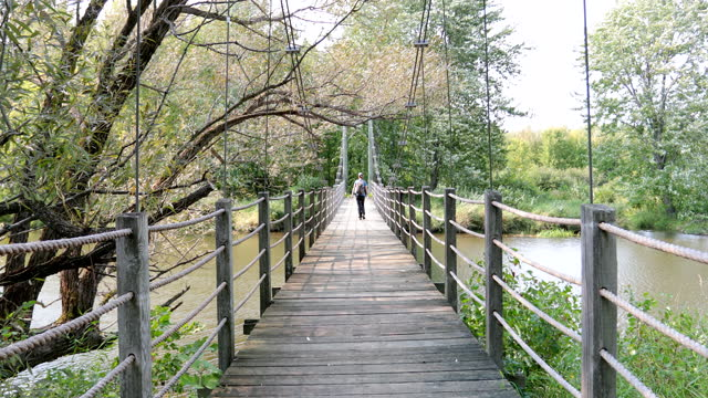 young woman walking on suspension bridge in summer - parc national stock videos & royalty-free footage