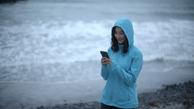 young woman walking on the beach during a storm - cappotto invernale video stock e b–roll