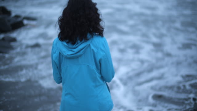 rv ms young woman walking on the beach during a storm - cappotto invernale video stock e b–roll