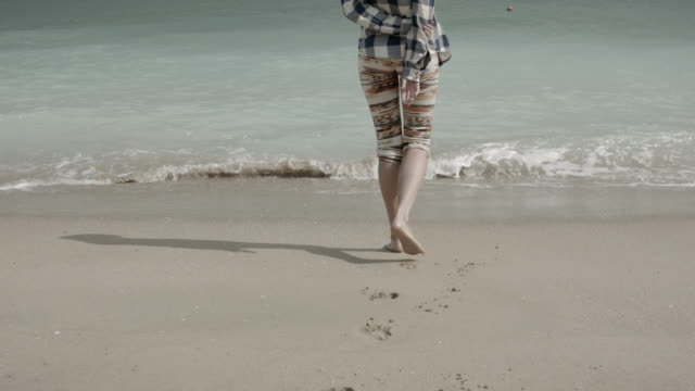 young woman walking on the beach in the black sea. - pants stock videos and b-roll footage