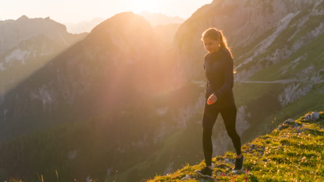 Young woman walking on the edge of a mountain