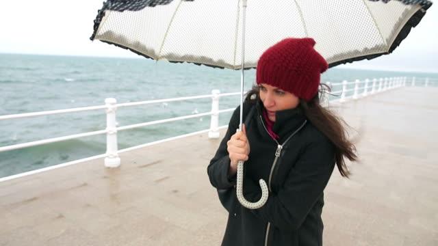 vídeos de stock e filmes b-roll de jovem mulher a andar na à beira-mar. - chapéu