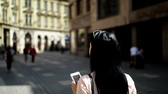 young woman walking on the street and using mobile phone - slow motion - vista posteriore video stock e b–roll