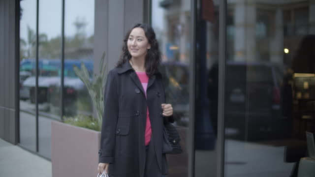 ms young woman walking on the street shopping - コート点の映像素材/bロール