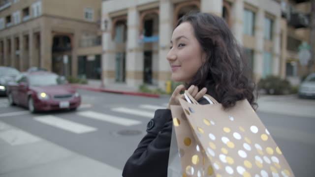 cu young woman walking on the  street with shopping bags - bärkasse bildbanksvideor och videomaterial från bakom kulisserna