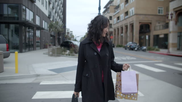 rv young woman walking on the street with shopping bags - コート点の映像素材/bロール