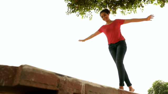 young woman walking on the wall, delhi, india - balance stock videos & royalty-free footage