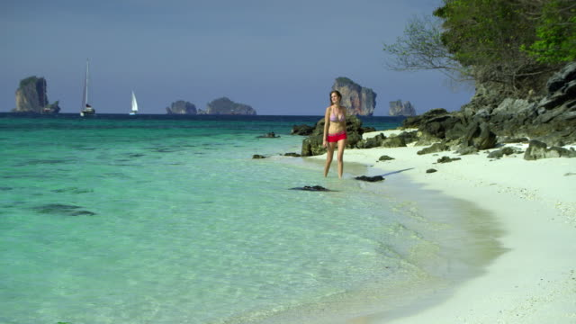 vidéos et rushes de ws young woman walking on tropical beach, krabi, thailand - s'approcher