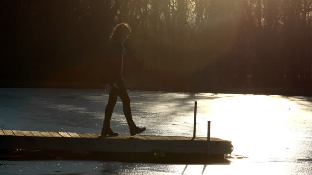 Young Woman Walking onto Dock