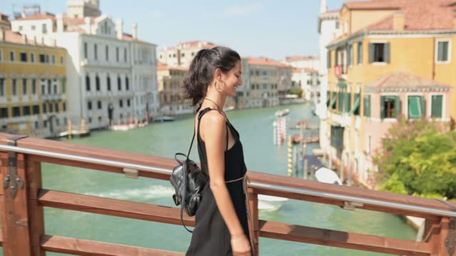 young woman walking over the bridge over grand canal in venice. - canal stock videos & royalty-free footage