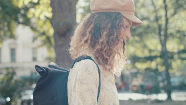 vídeos y material grabado en eventos de stock de young woman walking, smiling in sunshine in park in berlin - springtime