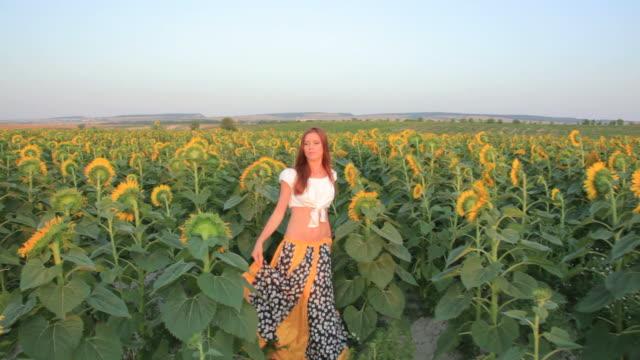 Junge Frau zu Fuß Sonnenblumen Feld bei Sonnenuntergang