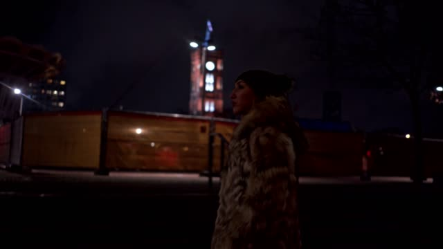 young woman walking the streets alone at night - winter coat stock videos & royalty-free footage