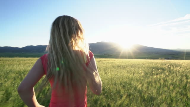 WS TS SM young woman walking through a field at sunset