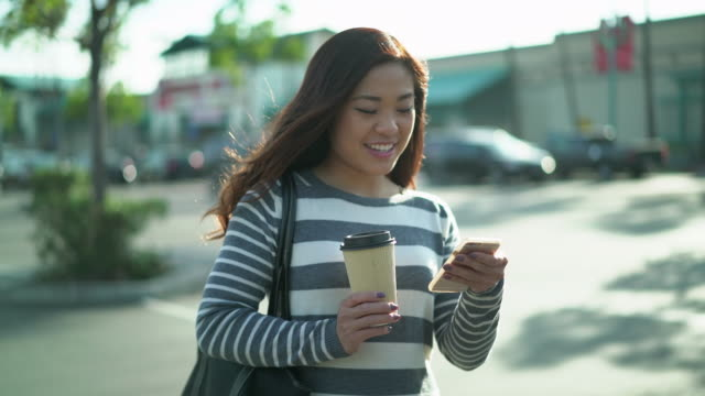 ms ts young woman walking through a parking lot holding a coffee cup and texting - parcheggio video stock e b–roll