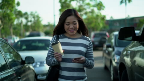 ms ts young woman walking through a parking lot holding a coffee cup - parking 個影片檔及 b 捲影像