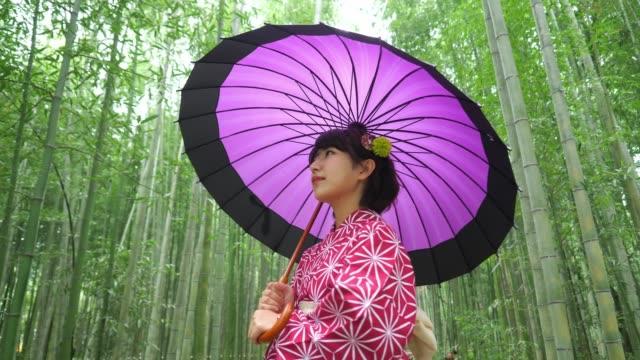 vídeos de stock e filmes b-roll de young woman walking through bamboo forest in kyoto - bamboo plant